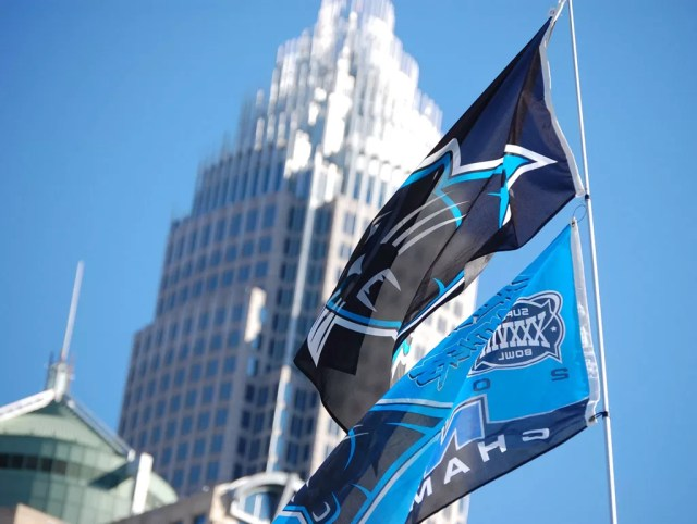 Carolina Panthers flag with Uptown Charlotte skyline in background