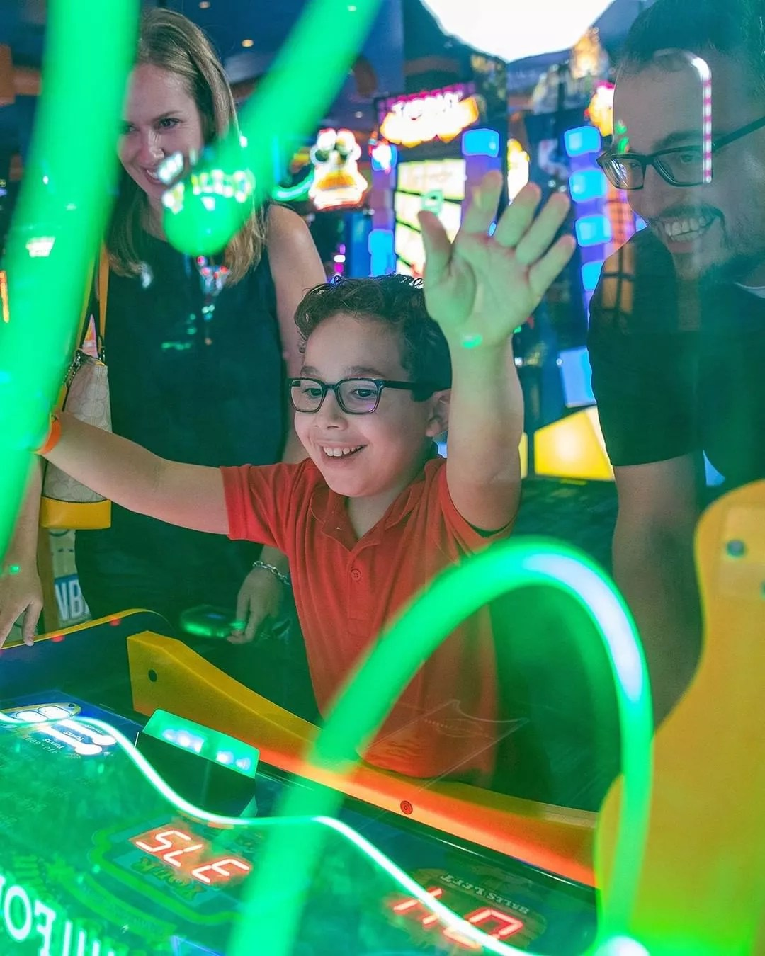 Little boy with parents playing at Dave & Buster's. Photo by Instagram user @daveandbusters
