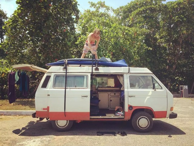 Man strapping surfboard to camper van. Photo by Instagram user @followthesol