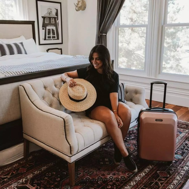 Young woman sitting in bedroom with suitcase. Photo by Instagram user @amtourister