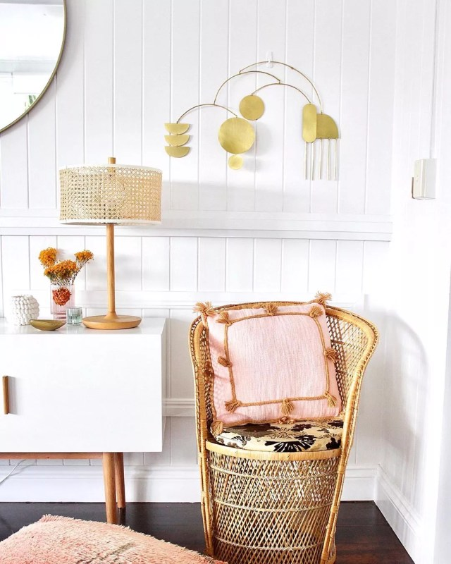 Wicker chair in corner of room next to console. Photo by Instagram user @k_bloves