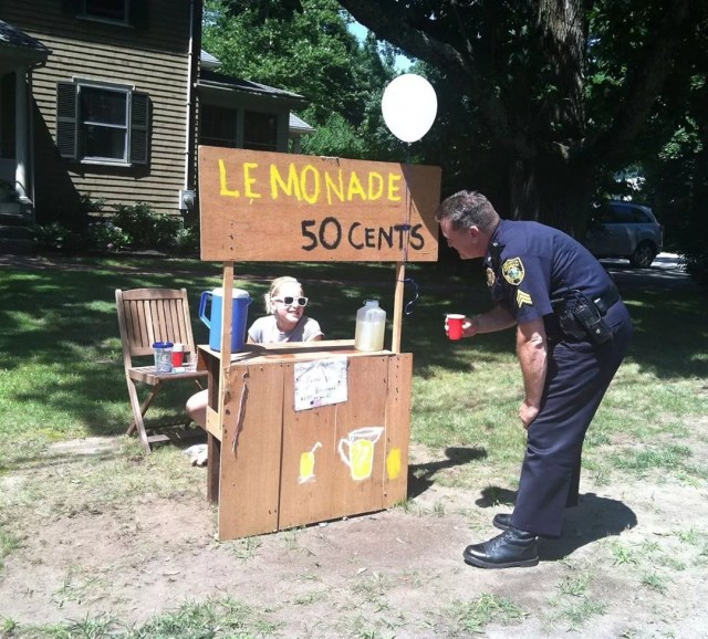 Policeman buying lemonade from lemonade stand. Photo by Instagram user @sgtstevendearth