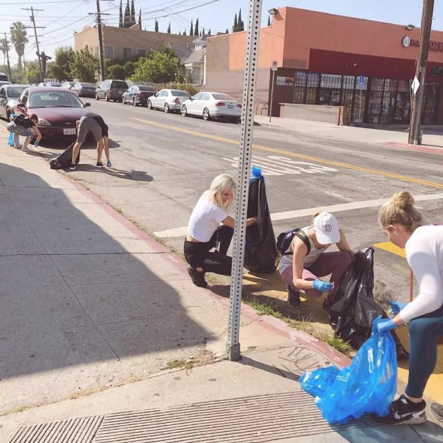 Group of people picking up litter on sidewalk. Photo by Instagram user @samarasacenter