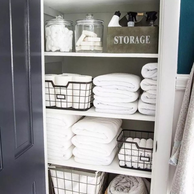 Folded Towels and Metal Containers in Closet. Photo by Instagram user @onelessstressok