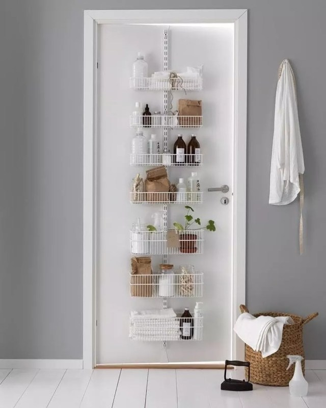 Bathroom Door with Hanging Rack Storing Cleaning Supplies. Photo by Instagram user @glasshouseintl