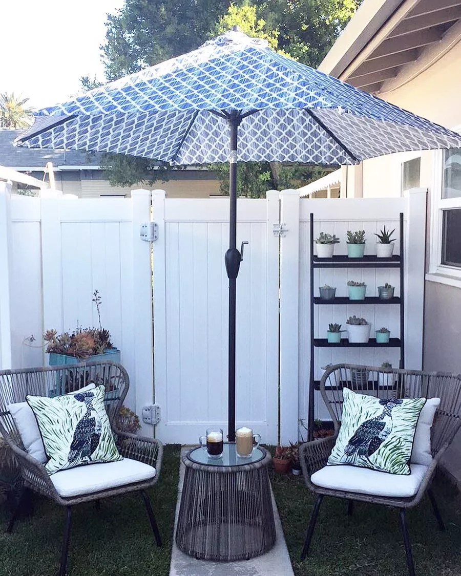 outdoor space with two chairs and small coffee table attached to an umbrella photo by Instagram user @homeobsession