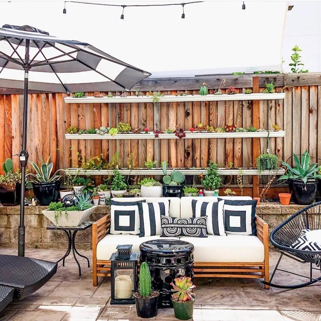 outdoor living space with vertical shelves acting as gardens photo by Instagram user @treehousethreadsblog