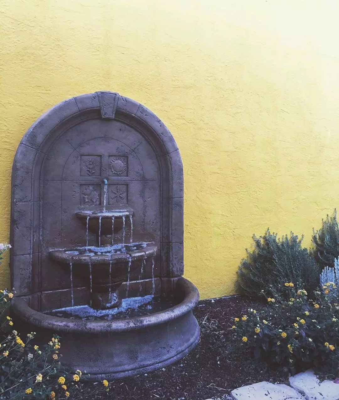 backyard fountain attached to a yellow wall in a flower bed photo by Instagram user @zjeepn.adventures
