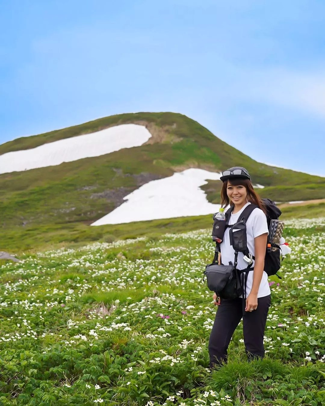 Woman with Backpack and Photography Equipment Hiking Through Green Hills. Photo by Instagram user @yumika0121
