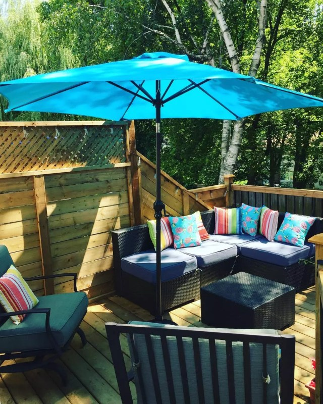 blue umbrella on a deck with seating around photo by Instagram user @gruth3