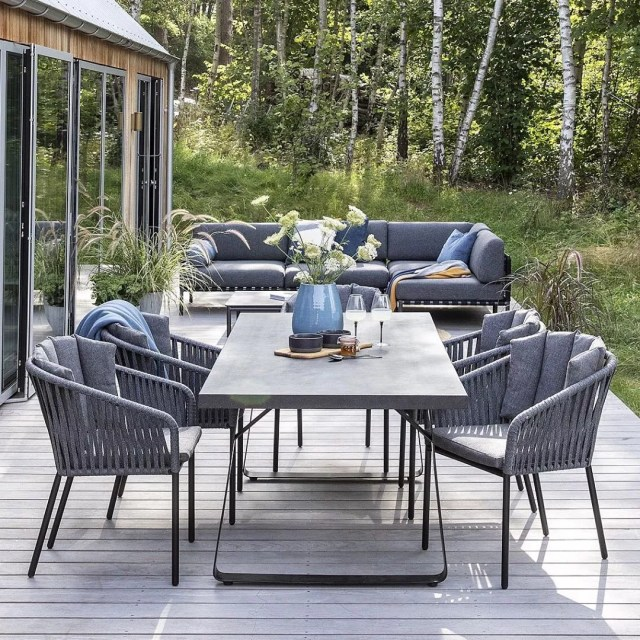 table and chairs and outdoor couch spaced on the deck photo by Instagram user @iddesign_hun