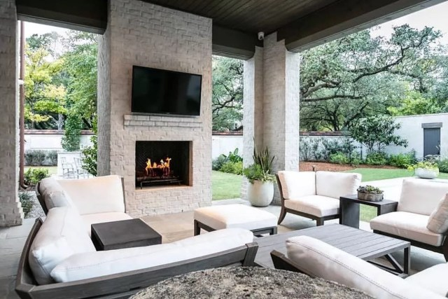 outdoor TV installed on outdoor fireplace with furniture all around photo by Instagram user @patioproductsusa
