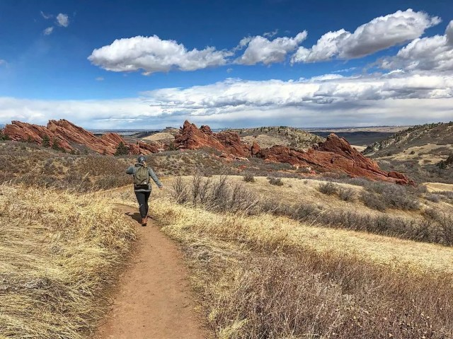 Woman walking on a dirt trail in outdoor Colorado with red rocks in the background Photo by Instagram user @melash