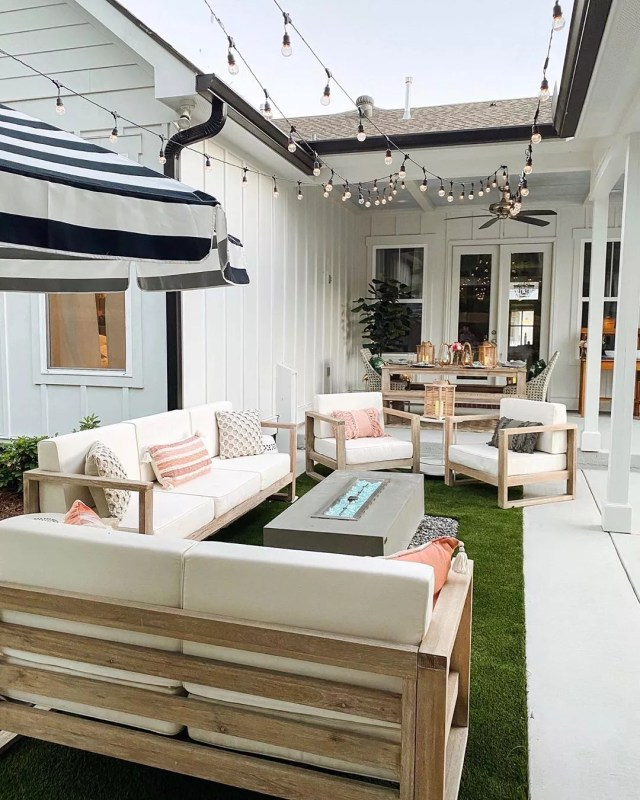 outdoor living area with seating and a fire table with string lights overhead photo by Instagram user @hauteofftherack