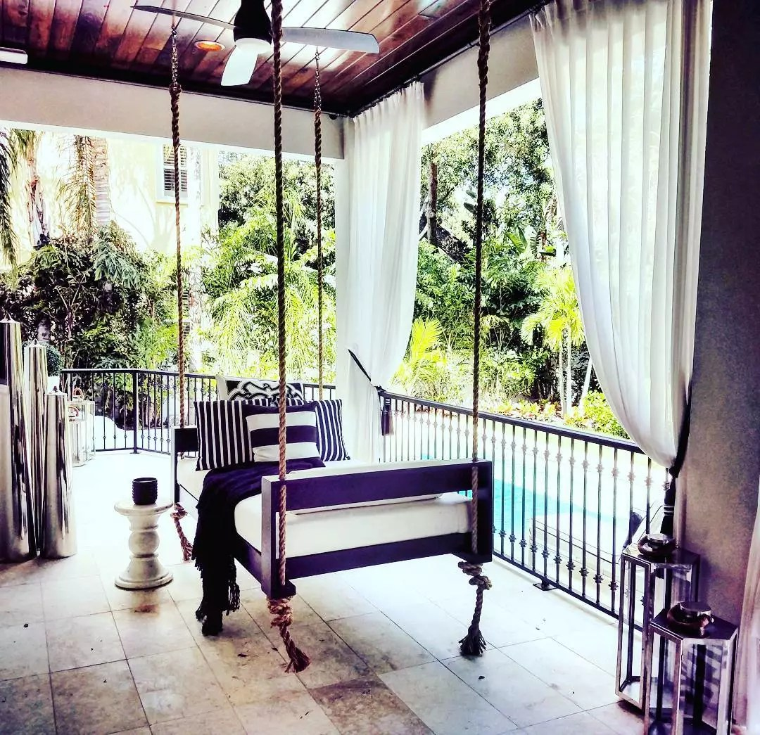 hanging bed set up on outdoor patio near pool photo by Instagram user @fouroakbedswings