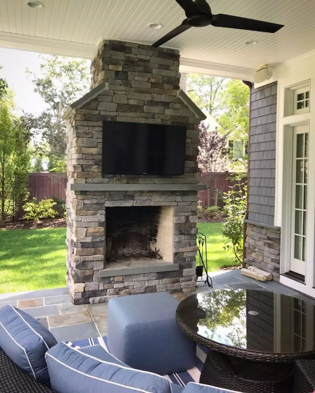 outdoor TV hanging from backyard fireplace with seating nearby photo by Instagram user @professional.audio.consultants