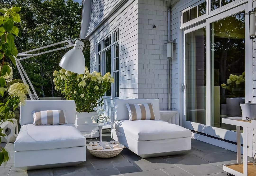 two chaise lounge chairs set up outdoors with a lamp overhead photo by Instagram user @baltimoredesigncenter