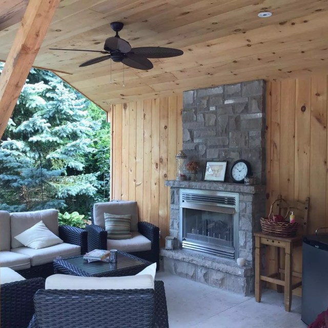 outdoor fireplace with fan on the ceiling and outdoor seating nearby photo by Instagram user @country_estates_landscaping