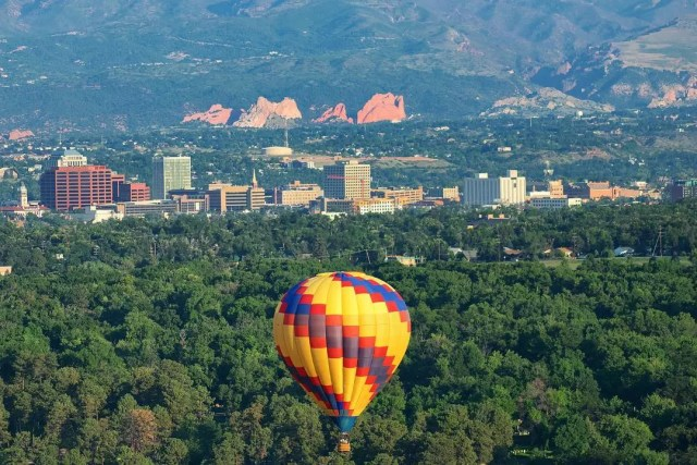 view of colorado springs from a drone with a hot air balloon photo by Instagram user @visitcos
