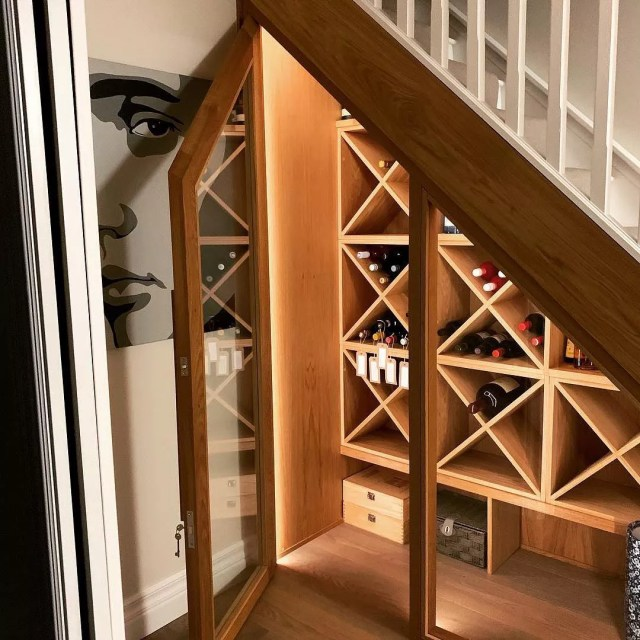 wine storage room with glass doors under the stairs photo by Instagram user @derekbarrettdesign