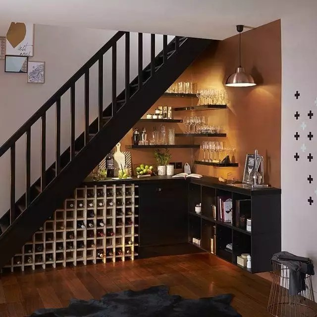 wet bar set up with glasses on floating shelves and wine storage under stairs photo by Instagram user @kappi.gh