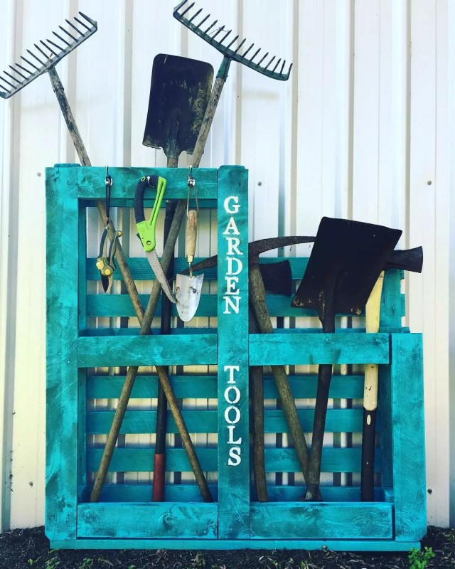 old wooden pallet with garden tools stored within it