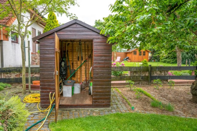 Outdoor shed with lawn and garden tools inside