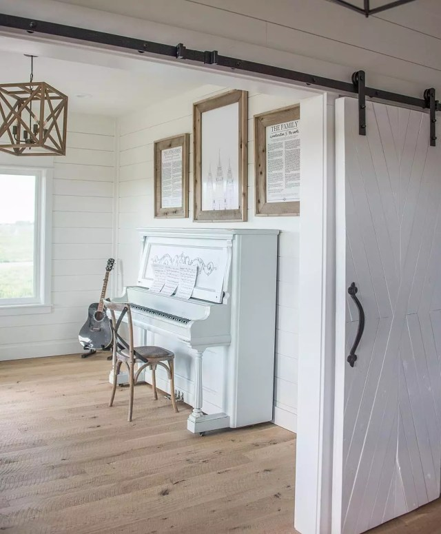 small music room with blue piano and sliding barn door photo by Instagram user @whitesparrowfarm