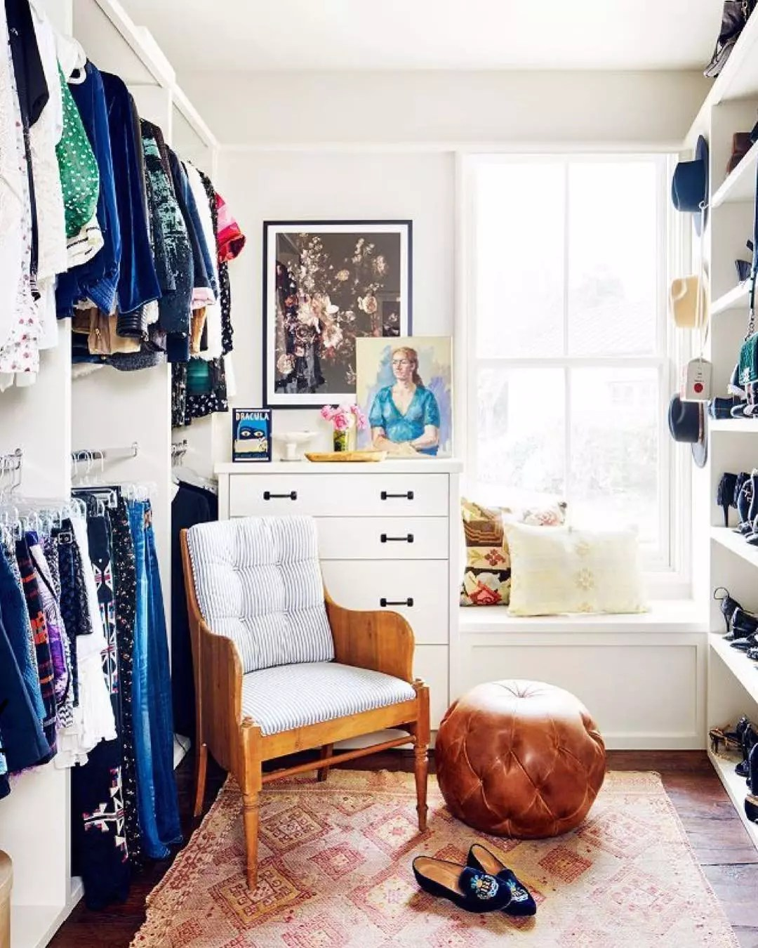 walk in closet with small chair and ottoman with dresser in the corner photo by Instagram user @house_of_merci