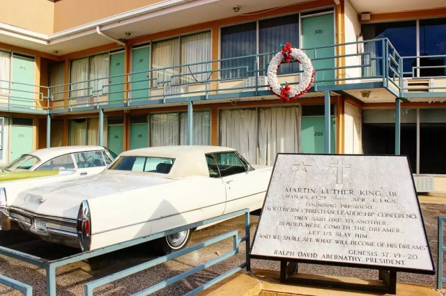 The Lorraine Motel and Martin Luther King Jr memorial plaque next to two cars and wreaths hangs from motel railings. Photo by Instagram user @licornephotography