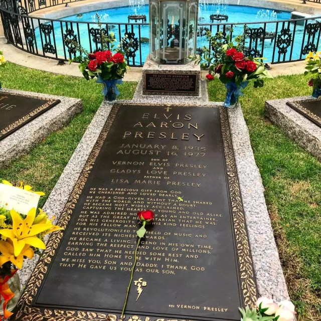 Elvis Presley's gravesite memorial with flowers at each corner and rose atop. Photo by Instagram user @ecrogers17