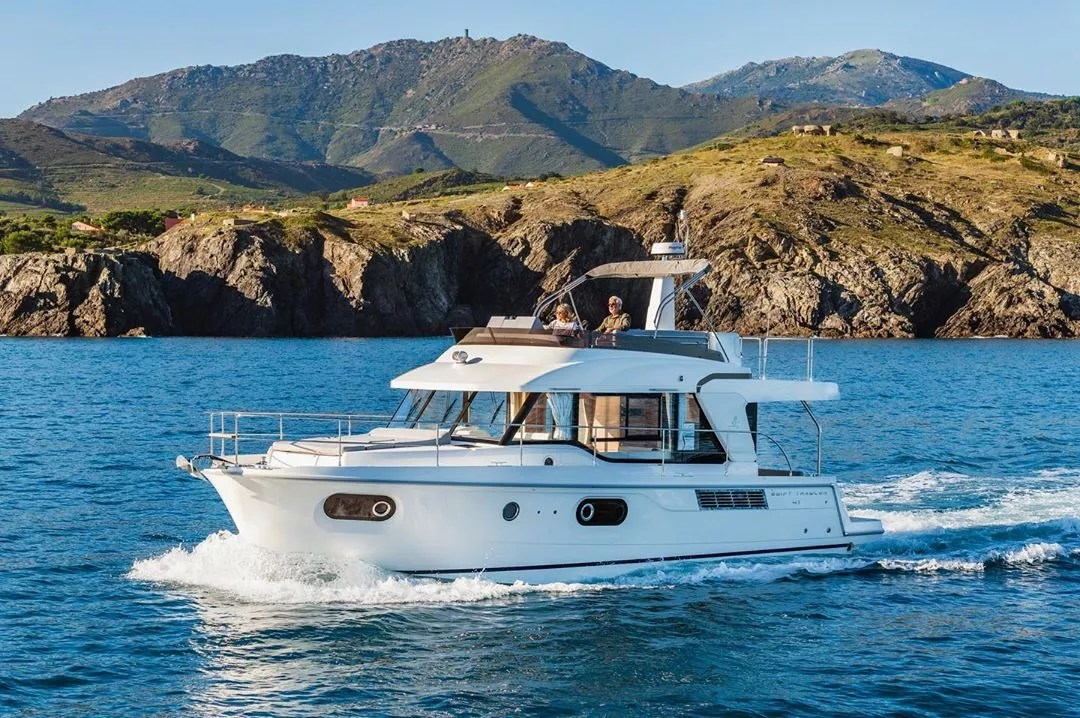 white beneteau swift trawler boat in the water with mountains in the back photo by Instagram user @beneteauamerica