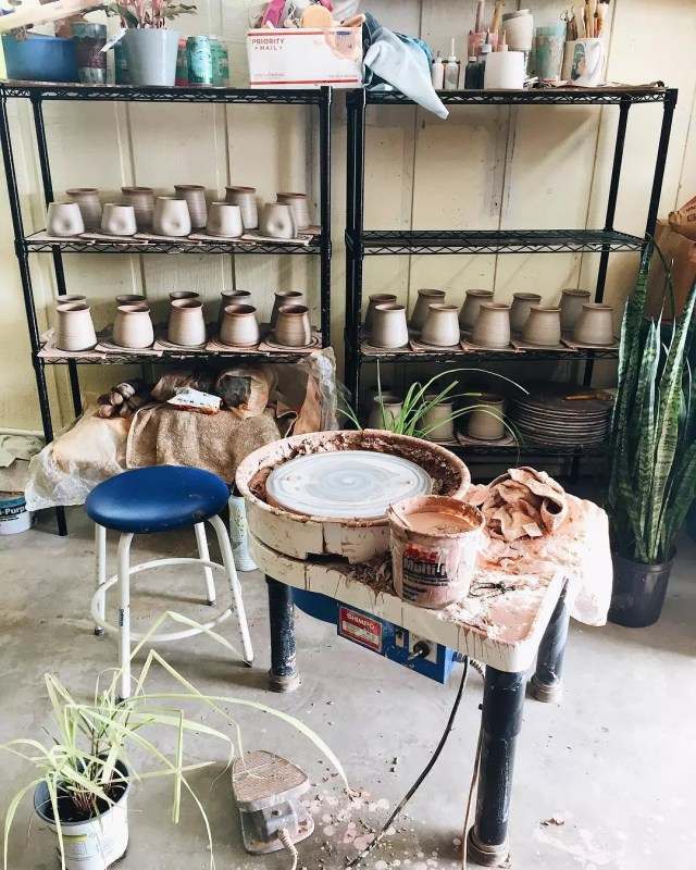 garage ceramics studio with wheel set up and shelves with supplies photo by Instagram user @swellceramics