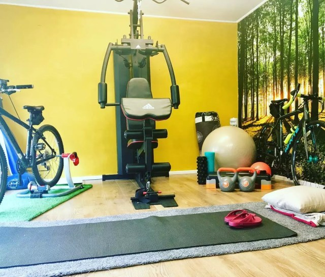 Home fitness room with bright yellow accent wall. Photo by Instagram user @thisgirlcanambassador