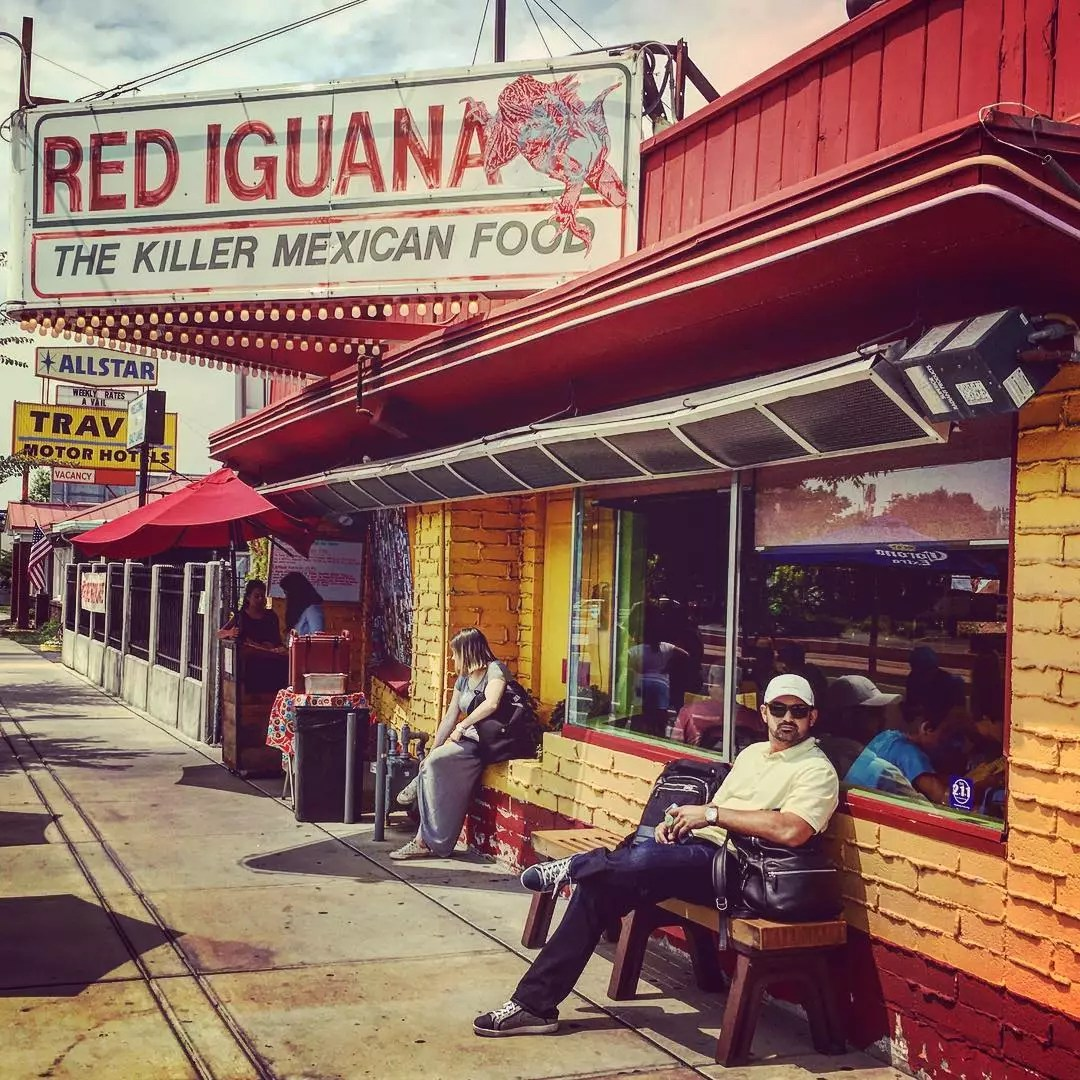 Man sits outside on a bench next to a mexican restaurant. Photo by Instagram user @adrian_eltitan