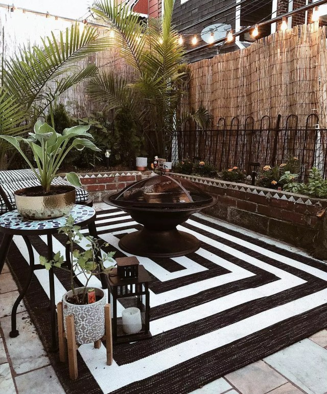 Patio with fire pit and black and white rug. Photo by Instagram user @alexandmike