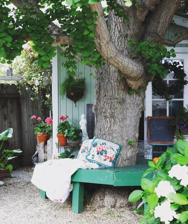 Green bench that wraps around a tree. Photo by Instagram user @cottagesandbungalows