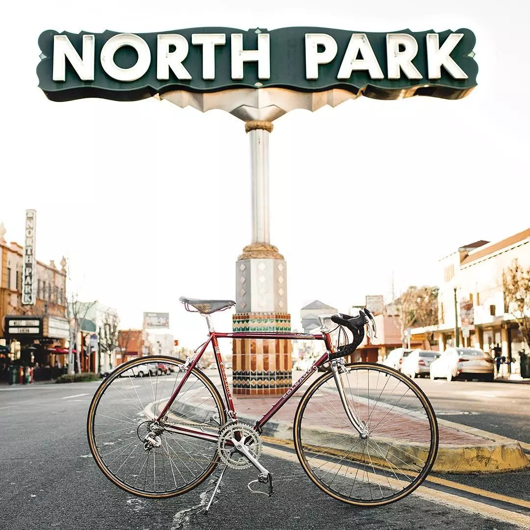 Bicycle parked beneath a North Park sign on a median of a street. Photo by Instagram user @explorenorthpark