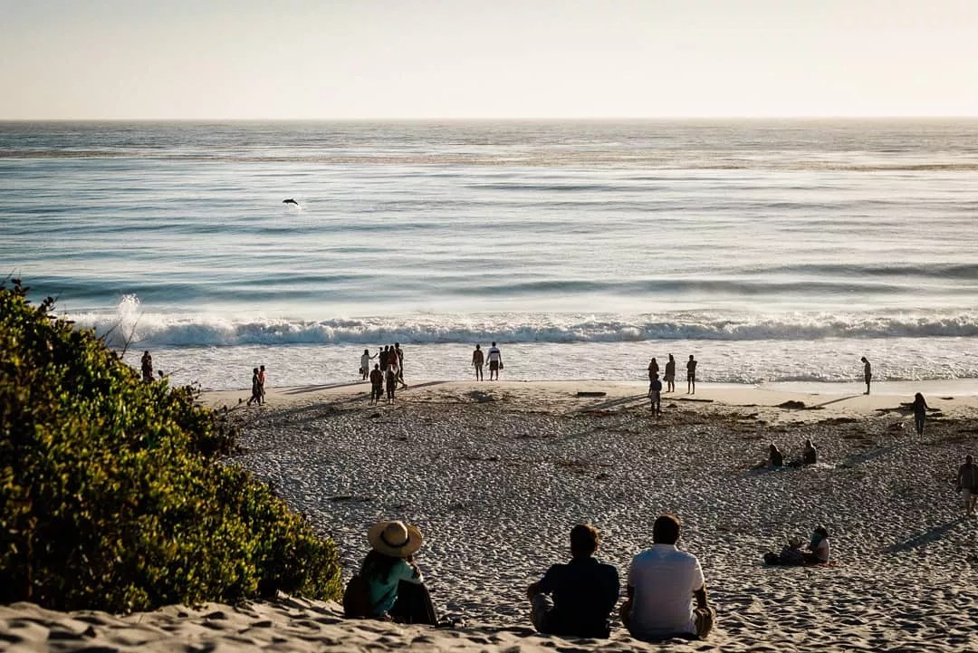 people sitting on the sand looking out at the ocean photo by Instagram user @emily_vista