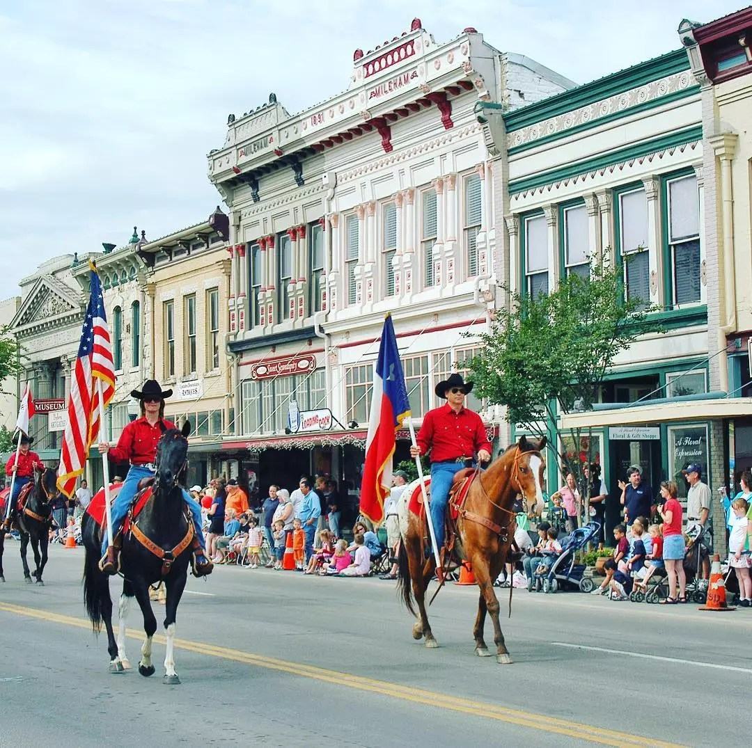 people on horses riding on main street holding texas state flag and american flag photo by Instagram user @georgetowntx