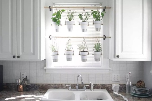 Hanging herb garden in white kitchen. Photo by Instagram user @hunkerhome