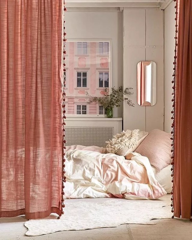 Pink curtains hiding bed area in studio apartment. Photo by Instagram user @urbanoutfittershome
