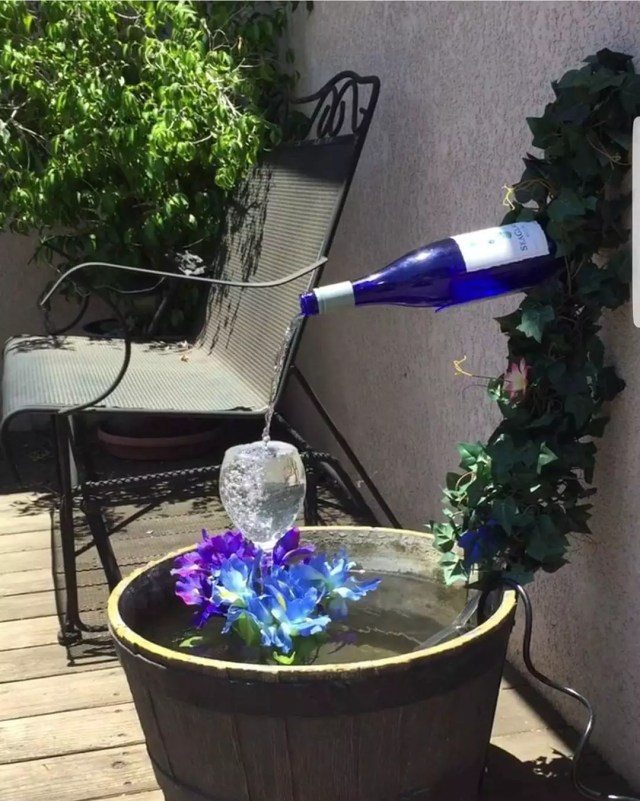 Porch fountain made from a blue wine bottle and wine glass. Photo by Instagram user @lisapalermorealtor