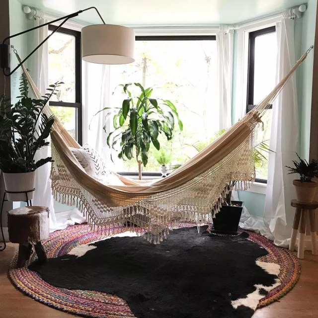 hammock strung across a room with lamp overhead photo by Instagram user @jandjdesignteam