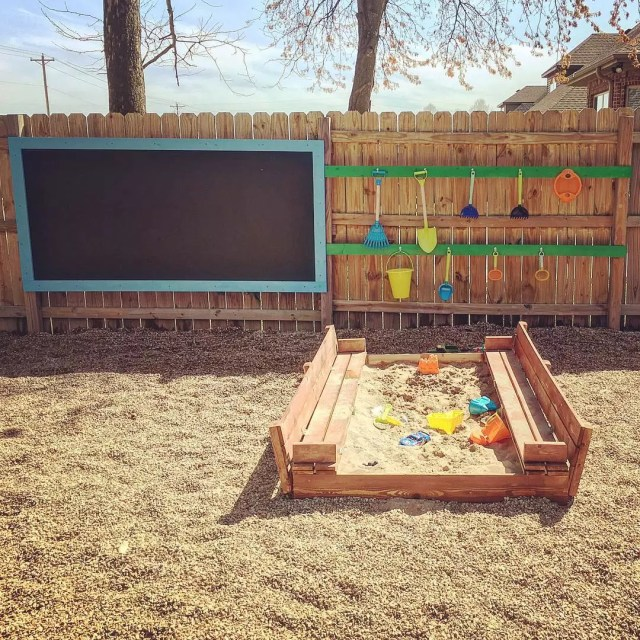 Sandbox with wall chalkboard in backyard. Photo by Instagram user @jnbennet