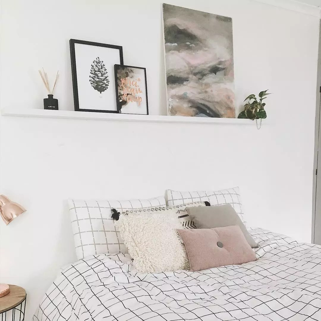 Floating shelves with home decor over bed. Photo by Instagram user @nocoffee_plz
