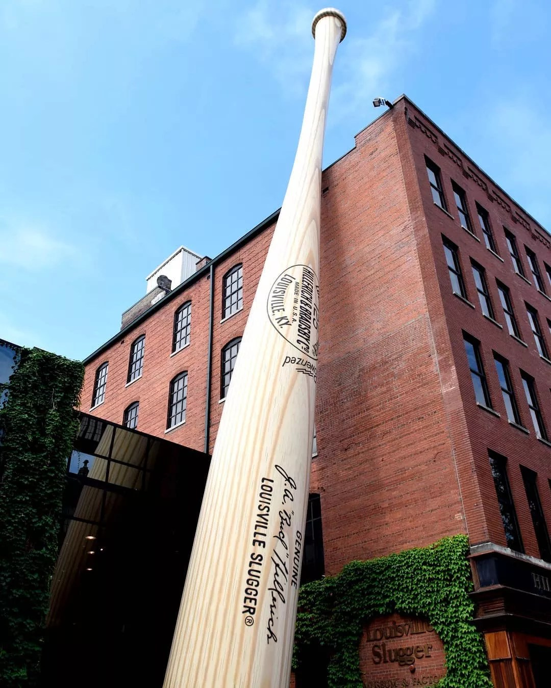 Looking up at a giant bat statue that leans against big red brick Louisville Slugger Museum & Factory. Photo by Instagram user @styleblueprint