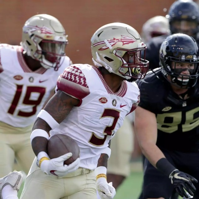 Florida State University football player holds the ball with other players behind him. Photo by Instagram user @cfbforever