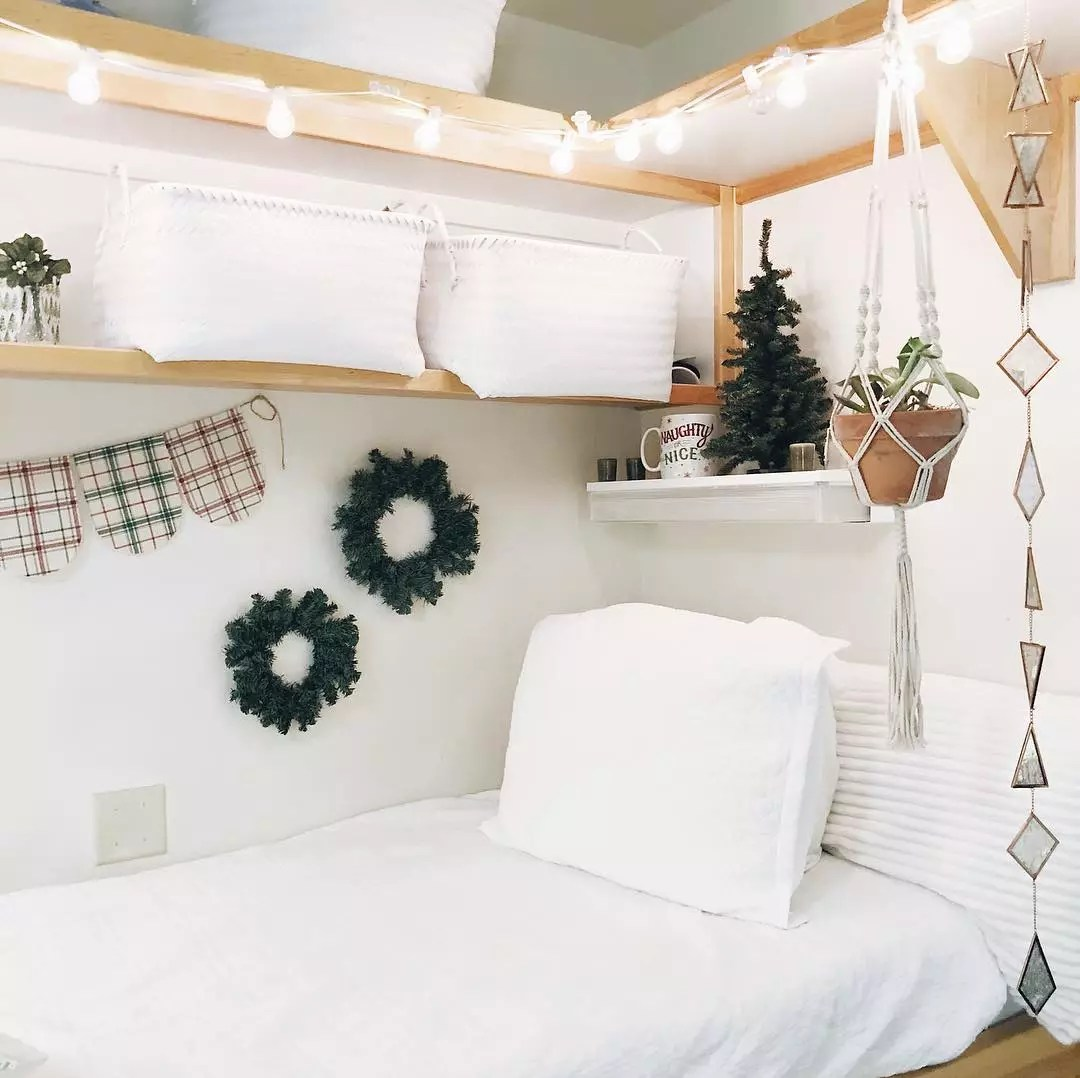 Open shelving with storage bins and decor over dorm room bed. Photo by Instagram user @emmagraceharrod
