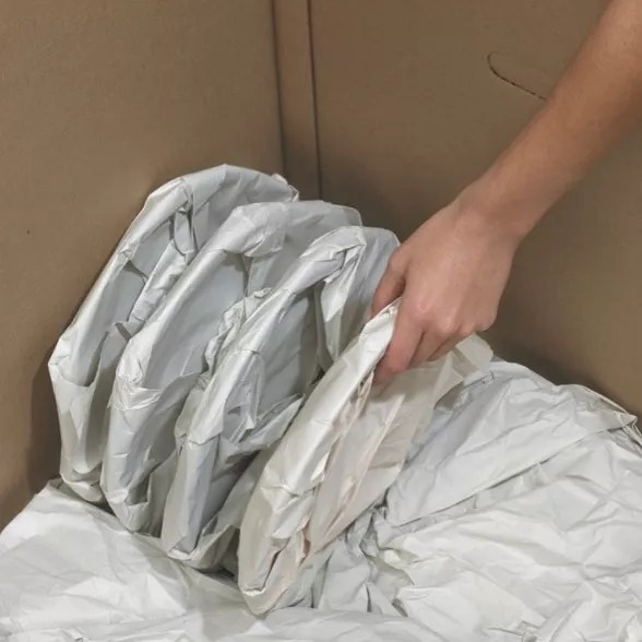 Dishes Heavily Wrapped in Paper Being Placed in Moving Box. Photo by Instagram user @lonestarrelo
